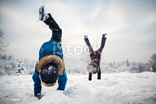 Little boy and his elder sister are enjoying the snow and the winter. Kids are doing handstands. Shot with Nikon D850 on cold winter day evening.