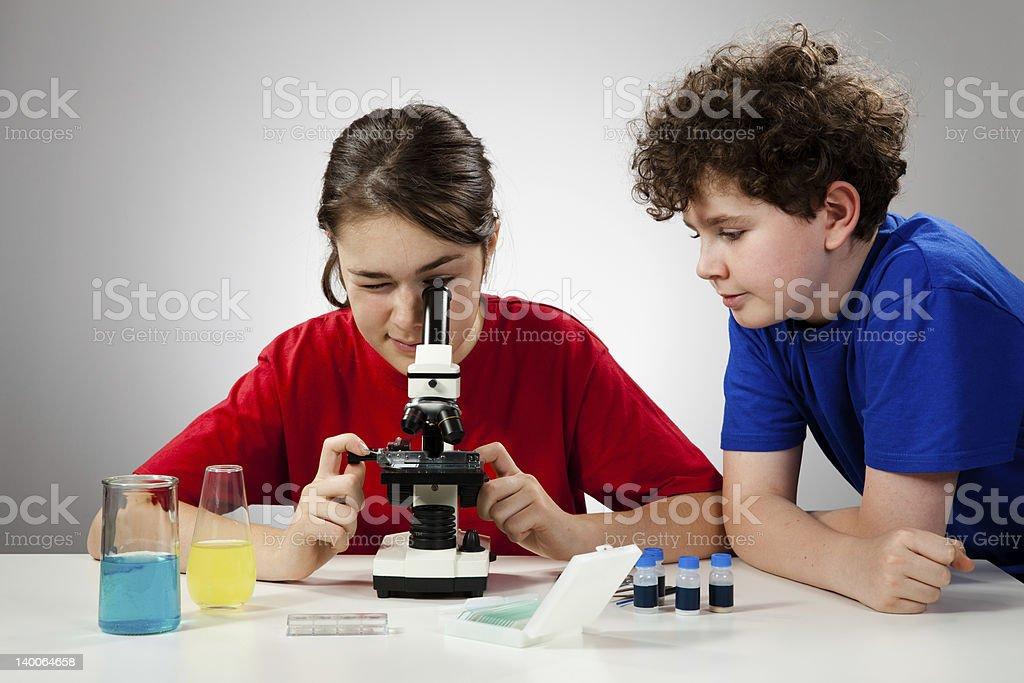 Kids examining something under microscope Girl and boy using microscope 14-15 Years Stock Photo