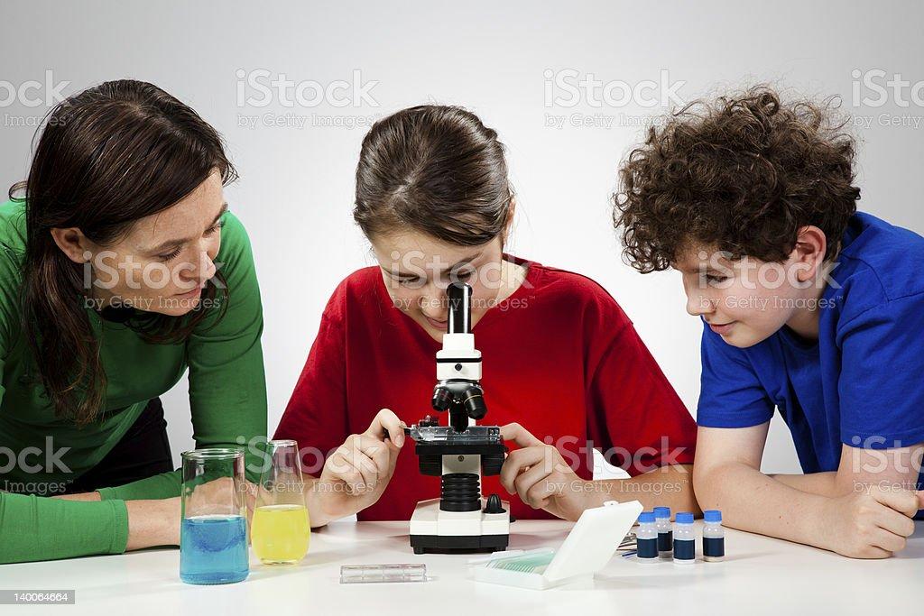 Kids examining something under microscope royalty-free stock photo