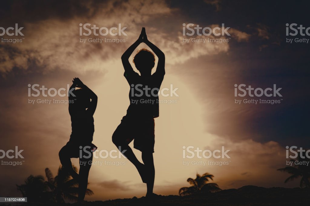 kids exercise at beach, boy and girl doing yoga at sunset