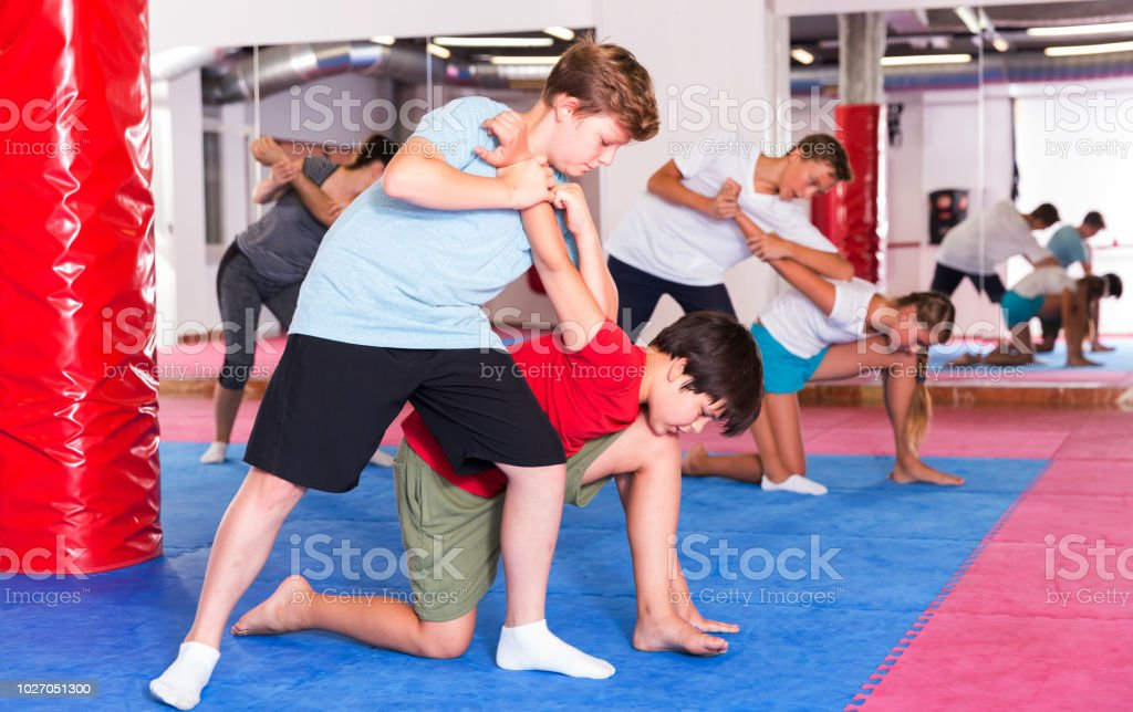 Adult and teen people practicing self defence technique in pairs at...
