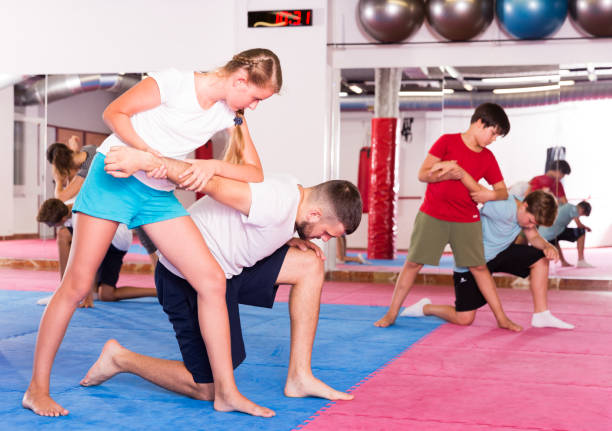 Kids exercising self-defense movements Kids with adults practicing effective techniques of self-defence in training room self defense stock pictures, royalty-free photos & images