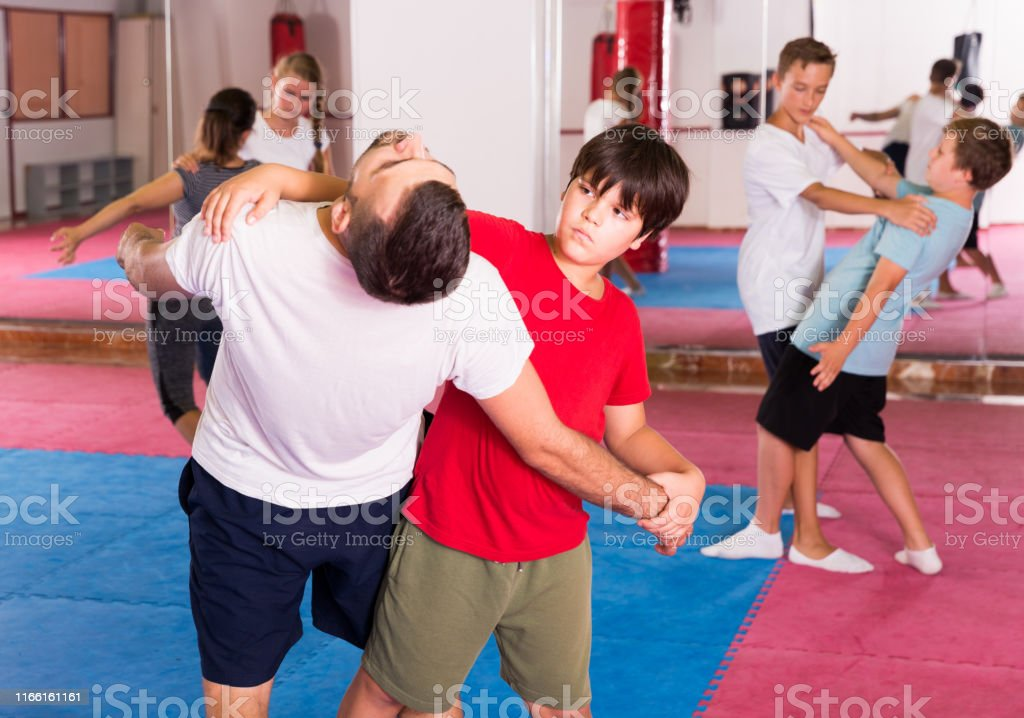 Kids with adults practicing effective techniques of self-defence in...