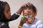 8 years old girl painting on 4 years old toddler's  face. Little girl getting butterfly face painting.