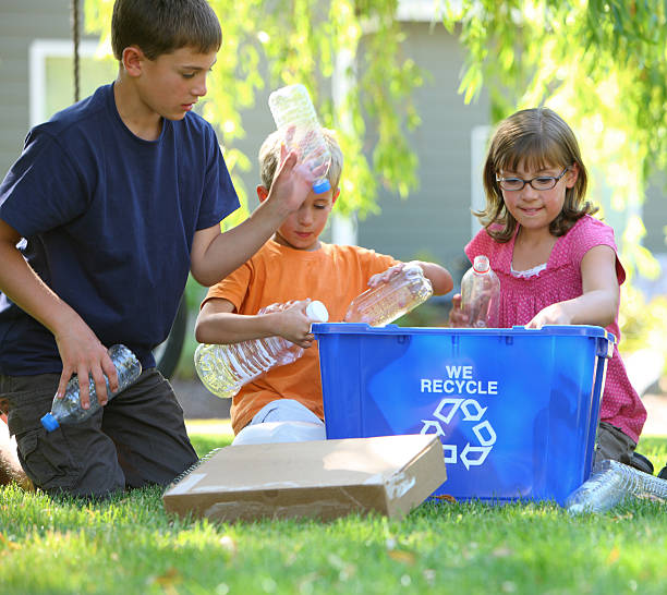 Kids filling recycle bin  bottle bank stock pictures, royalty-free photos & images