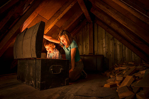 kids finding a treasure chest at the attic two surprised kids opening a glowing treasure chest at the attic of an old house attic stock pictures, royalty-free photos & images