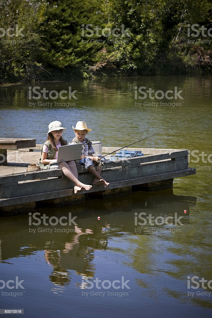 Kids fishing at a lake with computer foto stock royalty-free