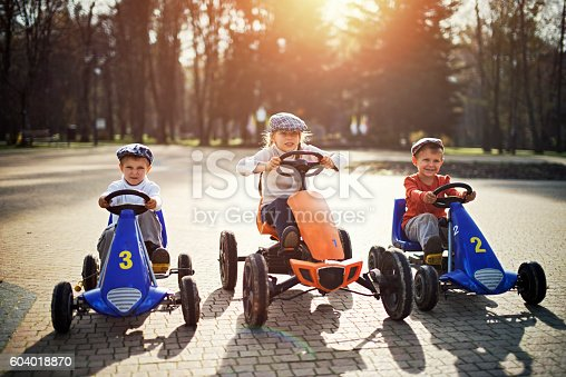 Three kids getting ready to start in a retro go-kart race. Gids are grabbing the steering wheels and focusing.  Sunny day.