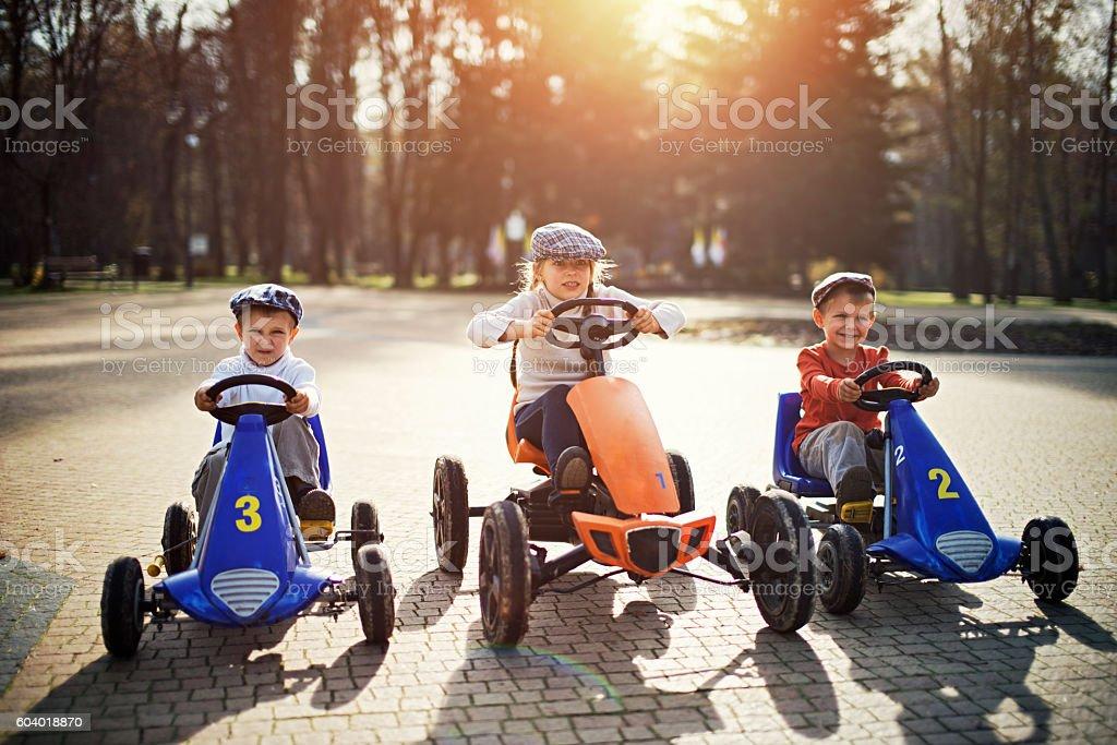 Kids getting ready to retro go-kart race stock photo