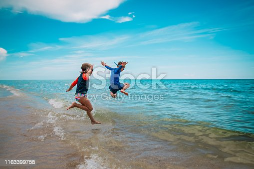 happy kids- girl and boy- run and play with waves on beach