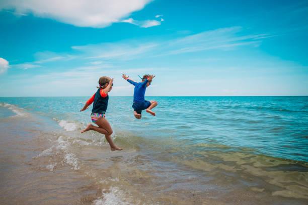 Kinder-Mädchen und Jungen- laufen und spielen mit Wellen am Strand – Foto
