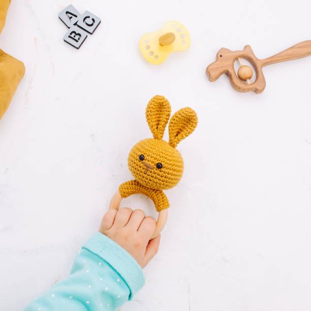 hand van de kinderen met bunny zitzak gemaakt van natuurlijke materialen op marmeren achtergrond - baby toy stockfoto's en -beelden