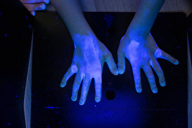 Kid's hand under the UV light revealing the only parts which have been correctly sanitised stock photo