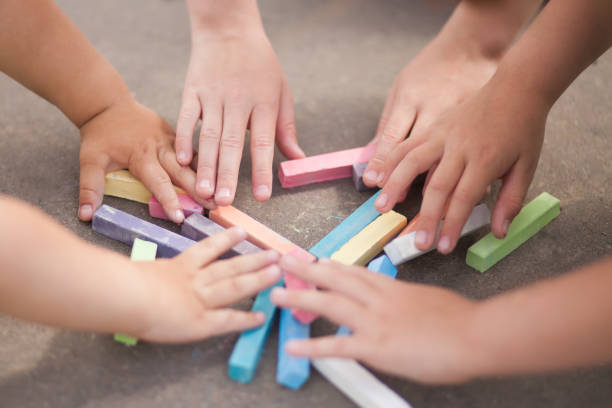 Kids hands and chalk, outdoors, closeup stock photo