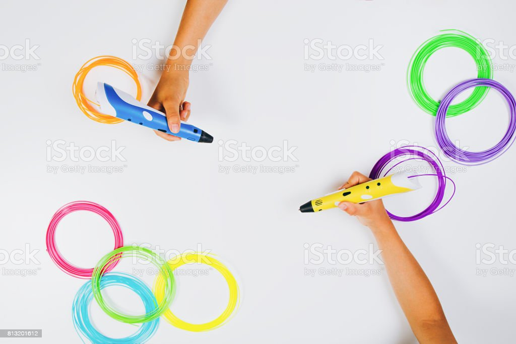 Kids hands holding 3d printing pens with filaments on white background. Top view stock photo