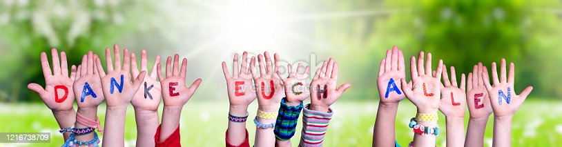 516544386 istock photo Kids Hands Holding Word Danke Euch Allen Means Thank You All, Grass Meadow 1216738709