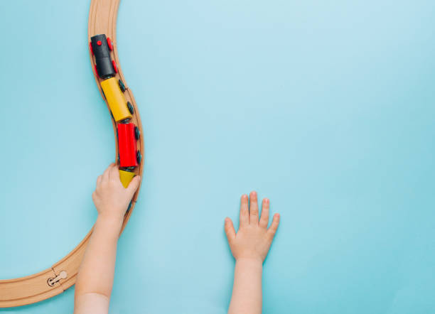 kids hands playing with wooden toy train on blue background - toy stock pictures, royalty-free photos & images