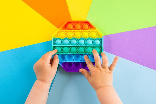 kids hands push sensory popit on colorfull background. Antistress pop it toy. Rainbow silicone sensory fidget New popular trendy silicone toy.