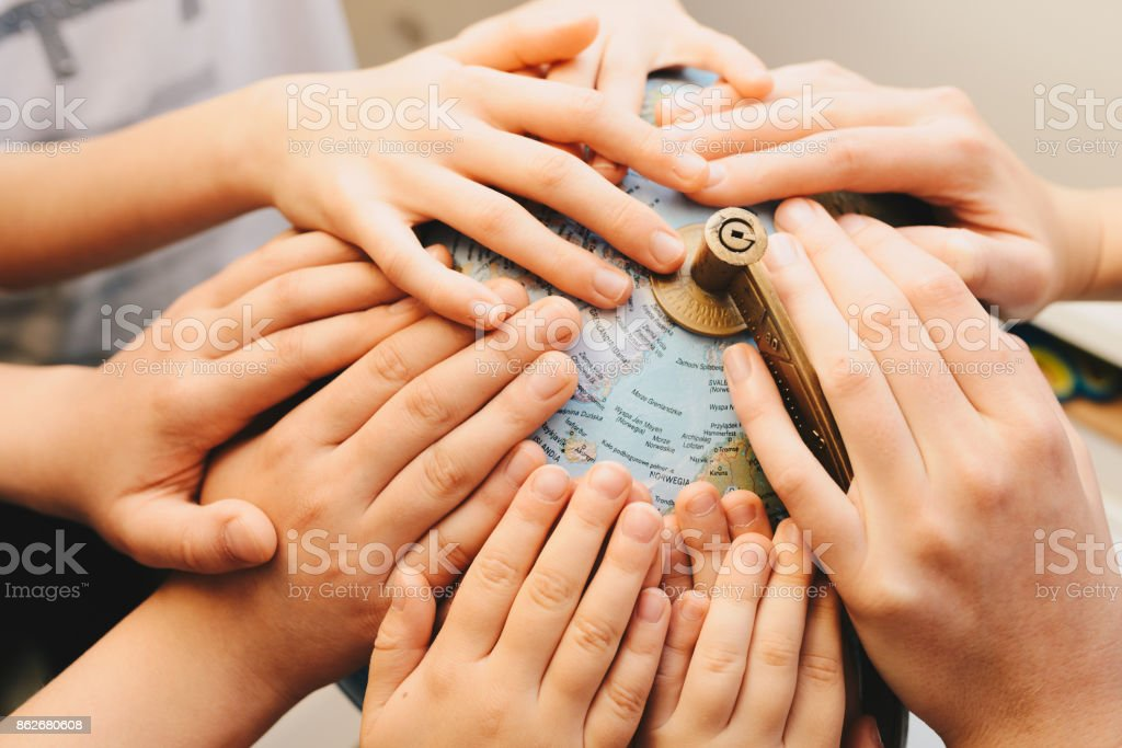 Kids hands together on globe - diversity concept stock photo