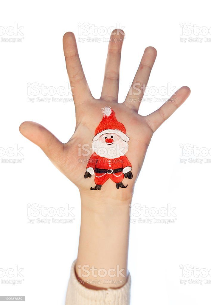 Kid's hands with painted Christmas symbol. Santa stock photo