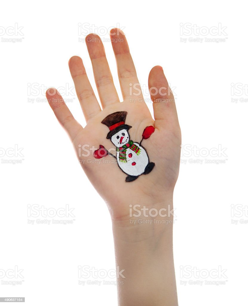 Kid's hands with painted Christmas symbol. Snowman stock photo