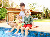 Kids splashing the pool water while sitting on edge with father