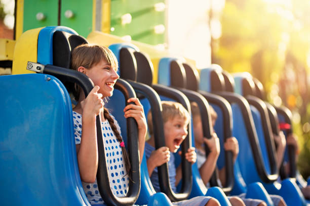 Kids having extreme fun in amusement park drop tower Kids being dropped down in a small drop tower in amusement park. Kids are laughing and shouting on a sunny summer day. amusement park stock pictures, royalty-free photos & images