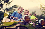Kids having fun in a small roller coaster in amusement park. Kids are laughing and shouting on a sunny summer day.