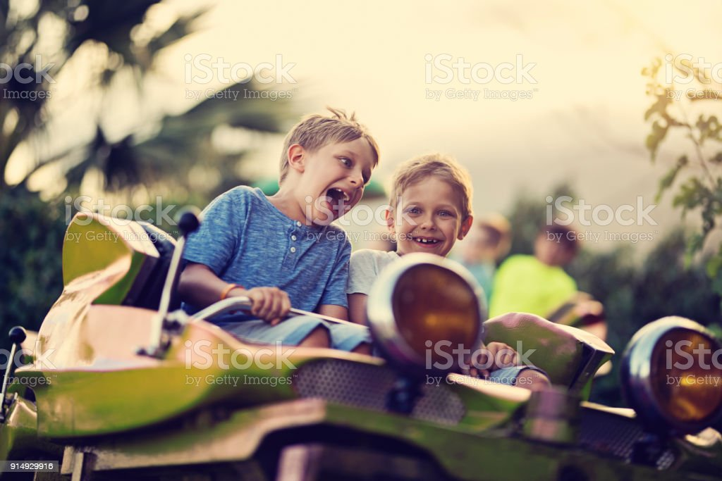 Kids having extreme fun in amusement park roller coaster stock photo