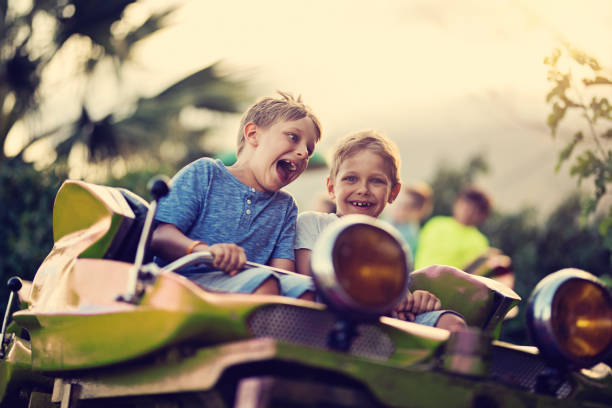 Kids having extreme fun in amusement park roller coaster Kids having fun in a small roller coaster in amusement park. Kids are laughing and shouting on a sunny summer day. amusement park stock pictures, royalty-free photos & images