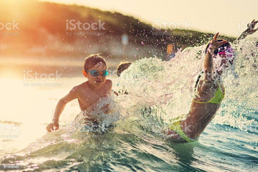 Kids having extreme splashing fun in the sea waves stock photo