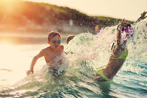 Kids having extreme splashing fun in the sea waves stock photo