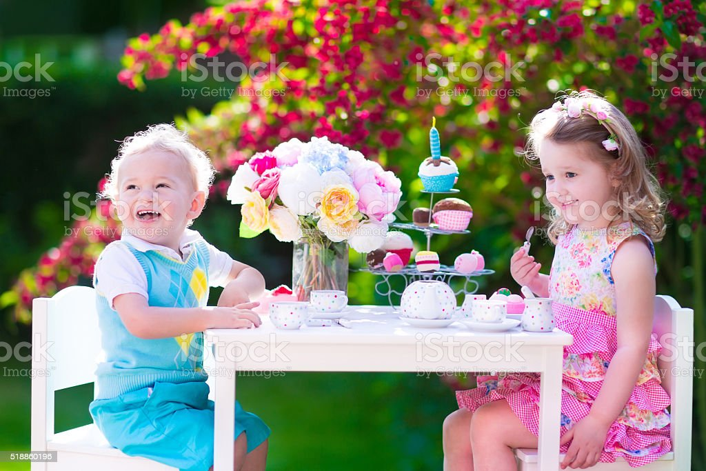 Kids having fun at garden tea party stock photo