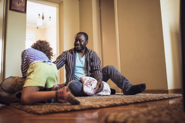 Kids having fun at home, playing with their father. stock photo