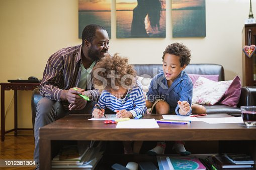 istock Kids having fun at home, playing with their father. 1012381304