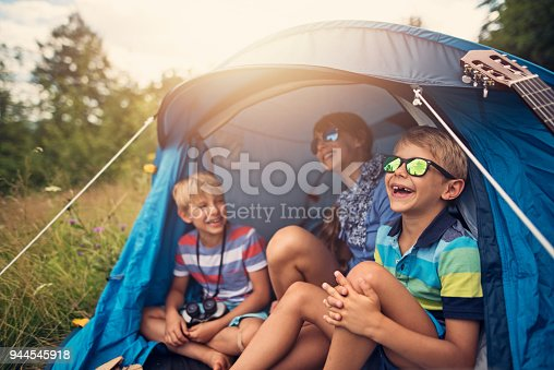 Little girl and her brothers are camping in a blue tent on the forest meadow. Kids aged 7 and 11 are laughing happily sitting inside of blue tent. Sunny summer day. Nikon D810