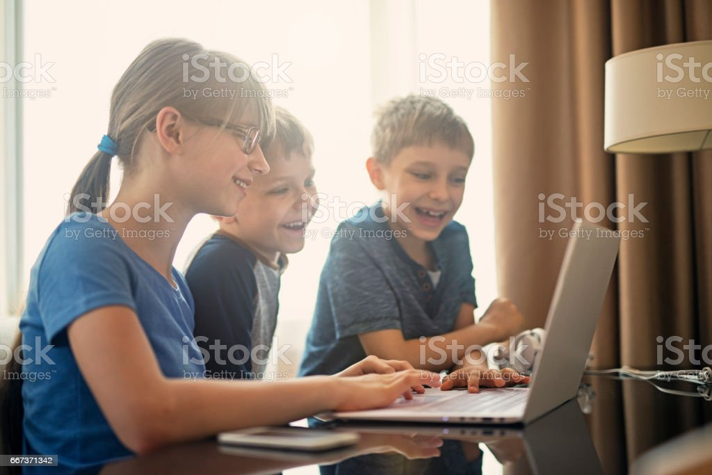 Kids having fun coding their homework at home stock photo