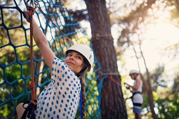 Niños divirtiéndose durante en el parque de aventura de cuerdas curso - foto de stock