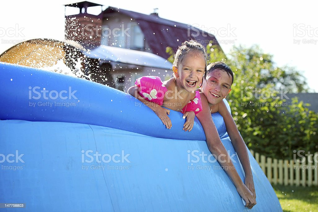 Kids having fun in a inflatable swimming pool stock photo
