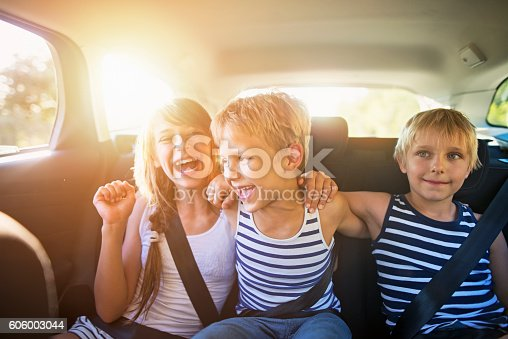 istock Kids having fun in car on a road trip 606003044