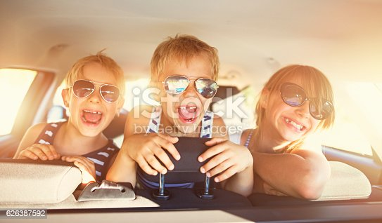 istock Kids having fun in car on a road trip 626387592