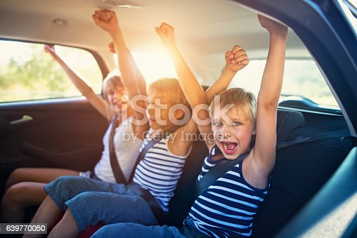 istock Kids having fun in car on a road trip 639770050