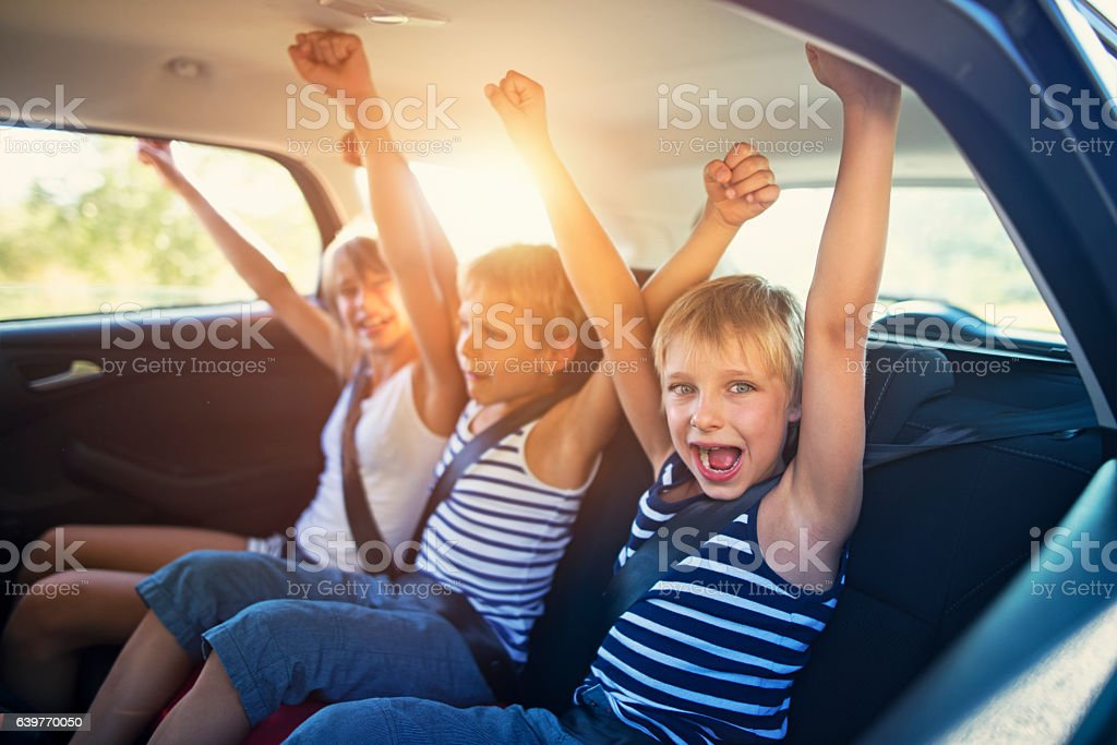 Kids having fun in car on a road trip stock photo