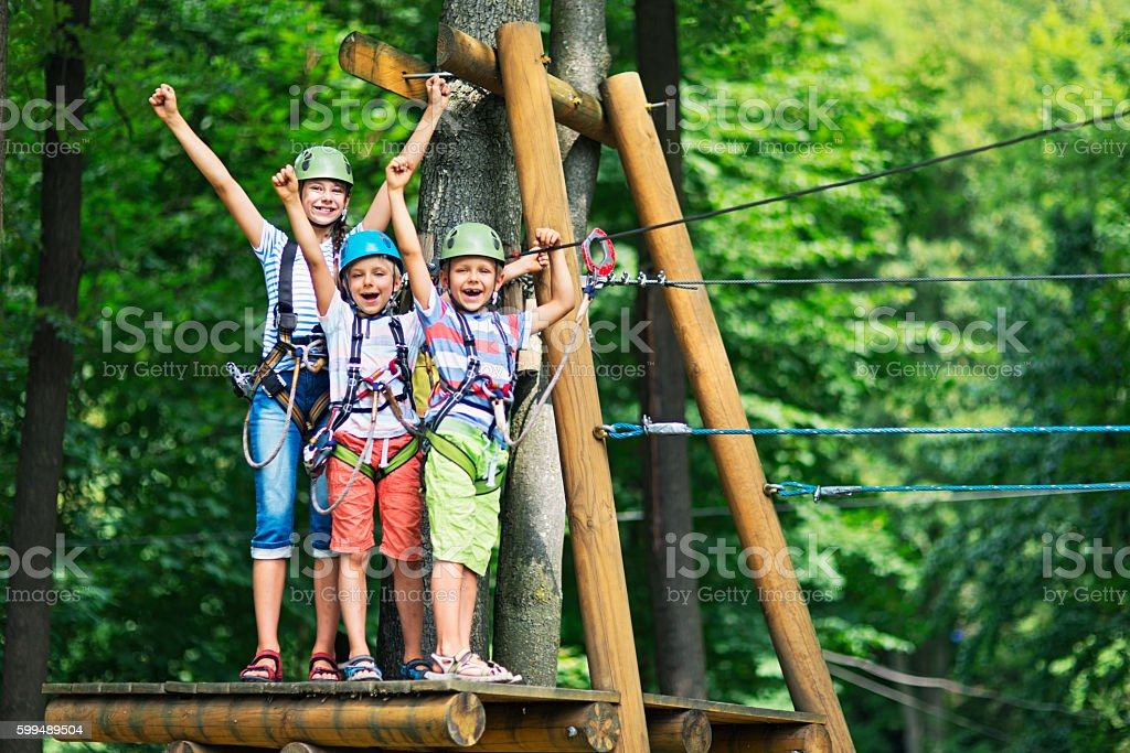 Kids having fun in ropes course adventure park - foto de acervo
