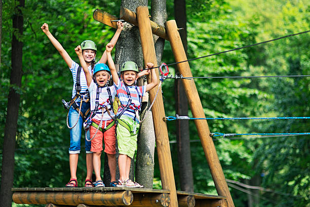Kids having fun in ropes course adventure park Little girl aged 10 with her brothers aged 7, wearing helmets stadning on wooden platform holding zip line in the outdoors ropes course adventure park. Kids are smiling at the camera and cheering. leisure equipment stock pictures, royalty-free photos & images