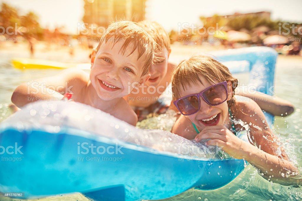 Kids having fun in sea on air bed stock photo