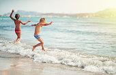 Kids jumping and having fun in the sea wearing ordinary swimwear.