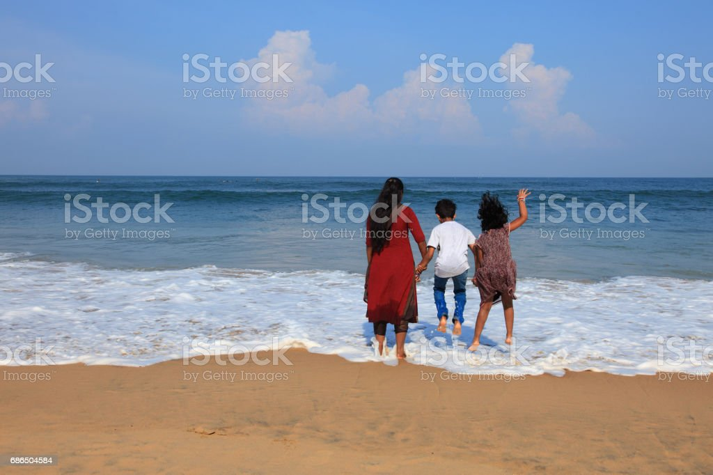 Kids having fun in the beach with their mother foto stock royalty-free
