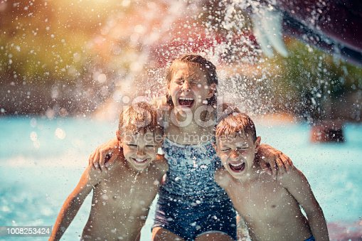 Kids having fun in pool in a waterpark. Laughing and screaming after being splashed with bucket of cold water. Nikon D850