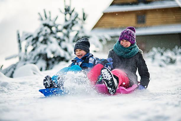 kids having fun  in winter sliding on snow with sleds - schneespiele stock-fotos und bilder